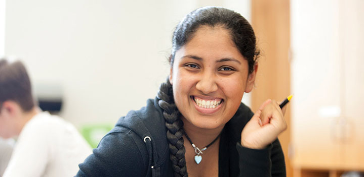 student smiling and holding pen in her right hand