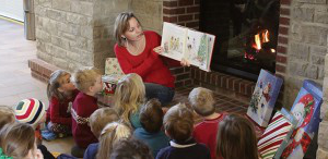 education student reading to preschoolers by the fire place