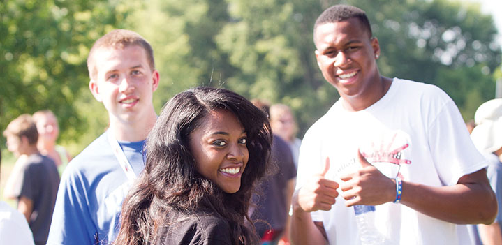 three students smiling during orientation activities