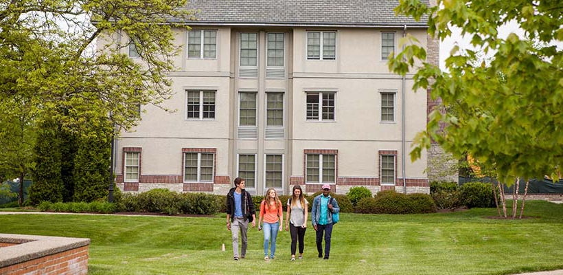 students walking across the green outside of the residence suites