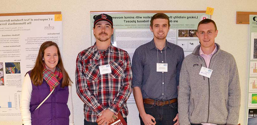four students present biology research posters