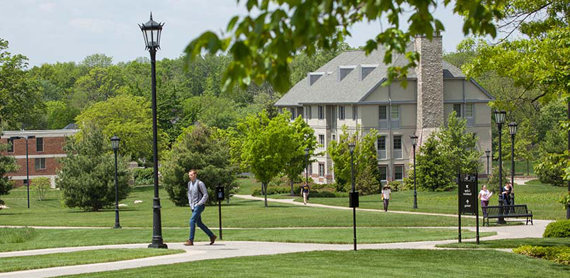 student walking in front of residence suites
