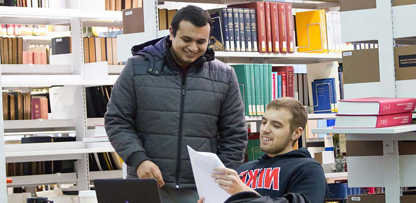 students reviewing papers in the library