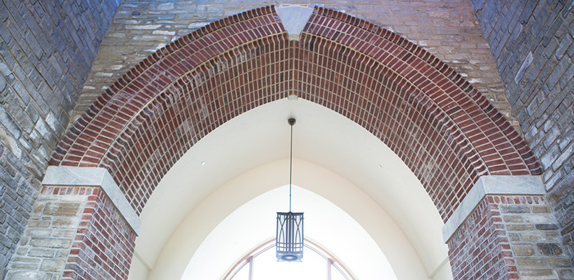 brick and stone archway with a hanging lamp