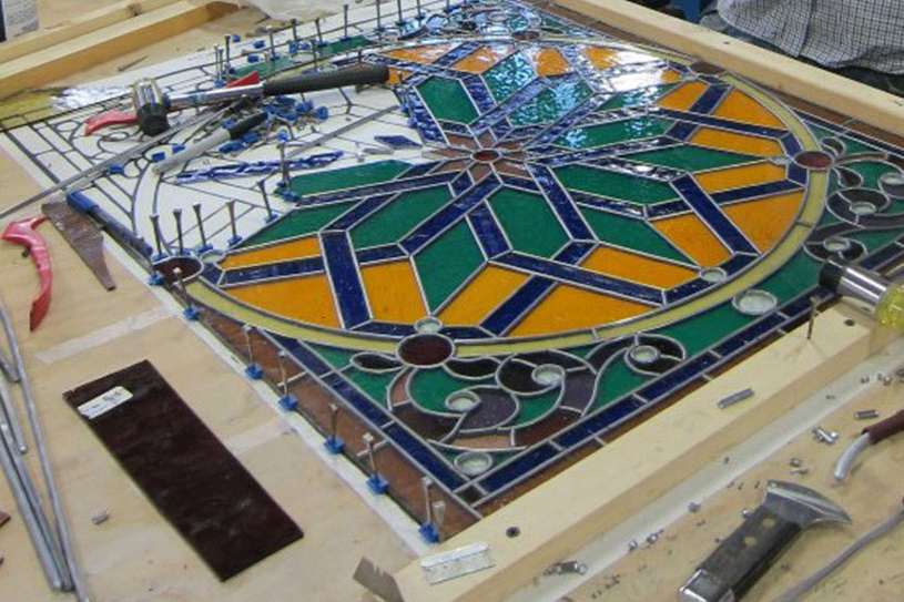 an intricate STained glass piece in the process of being put together