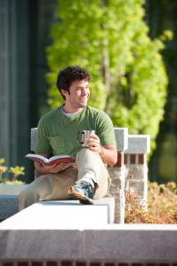 student sitting on a wall reading a book